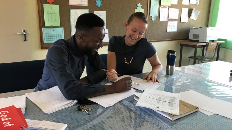 A man and a woman sit seated at a table. The table is strewn with papers, and they look to be working on an assignment togeth