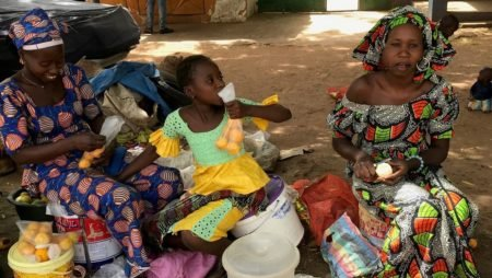 Two Gambian women sit outside at a market selling oranges.