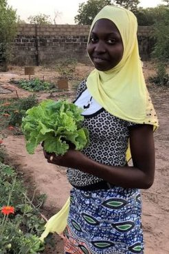 A young girl holds up a crop proudly.