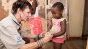 An older Peace Corps Volunteer shows a young girl how to use hand sanitizer. They're facing each other and their profiles are