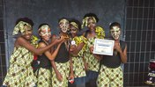 A school dance group shows off their award after a performance.
