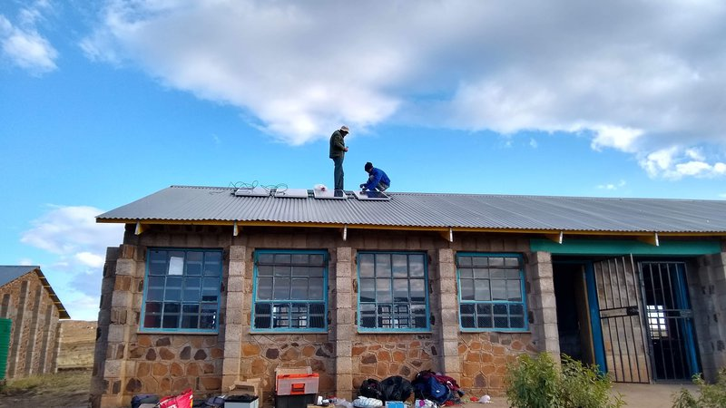 Two African men install solar panels on a school roof in Lesotho