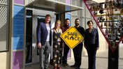 """Five coworkers pose for a picture outside of their office building. They are holding a yellow sign that says """"Safe Place"""""""