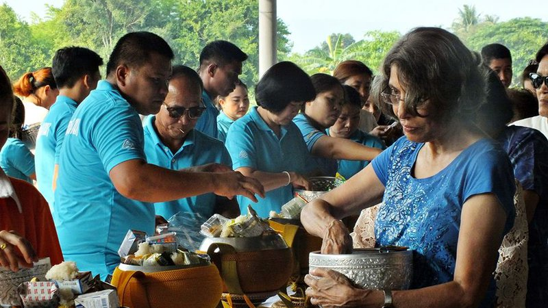 A Indian American woman mixes food in a pot standing up with many of her Thai friends. They are all wearing blue