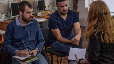 Three people sitting down talking