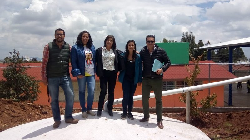 Volunteer Cassidy Pearson and collaborators pose on top of the 50,000 liter capacity water cistern.
