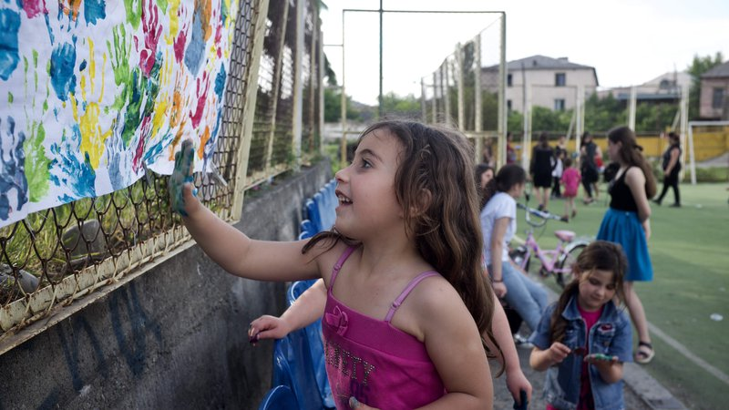 A young girl, hand covered in blue paint, adds her hand print to piece of paper with other colorful hand prints.