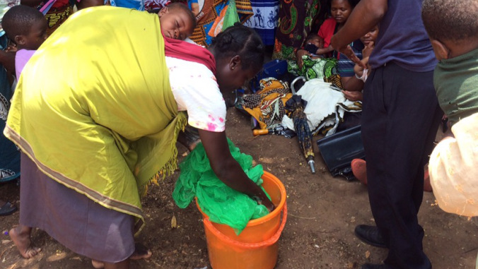 A Malawian community member washes her bednet at a demonstration by her Volunteer.