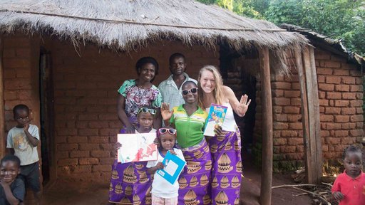 Health Volunteer Emma poses with her Malawain family--all wearing purple chitenje skirts.
