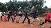 A group of teachers in Malawi hold hands in a line as they do a team building activity outside