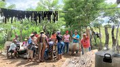 A group of Panamanians and a young white woman stand outside cooking in a big group, with smiles.