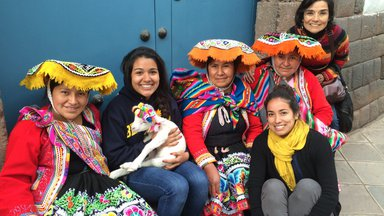 Fiorella sits with women in bright traditional Peruvian clothing with a small lamb on her lap