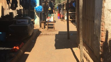 A classic Malawi market, complete with items to buy, thatch stands, and a dirt path in between.