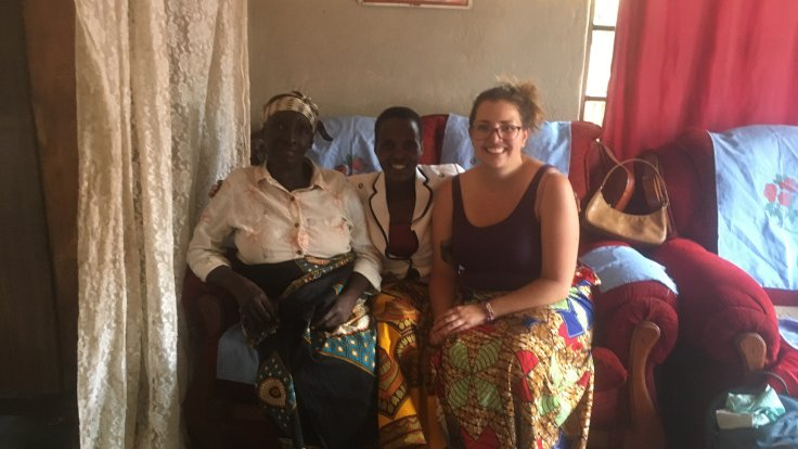 A white, female Volunteer sits smiling with two Malawian women on a sofa chair.