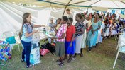 Volunteer Anna hands out bed nets to a line of Malawians.