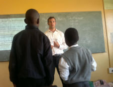 Peace Corps volunteer Chris Ames quizzes South African students in a math competition he organized with Genna Cummins.