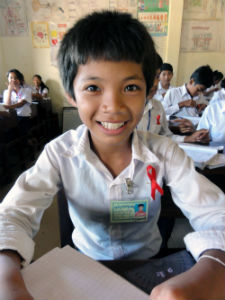 People's Choice Winner. A student at a primary school in Cambodia shows his AIDS ribbon as he awaits a presentation on HIV/AIDS for World AIDS Day 2011. Photo by Peace Corps volunteer Matthew Dantism (Cambodia, 2011-2013).