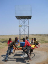 Children in Peace Corps volunteer Andrew Hubble's South African community pump water on the merry-go-round pump.