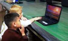 Two Jordanian children learn to use a computer during a training held by Peace Corps volunteers.