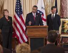 Peace Corps Director Aaron S. Williams speaks about the Peace Corps legacy at the State Department. Under Secretary of Public Diplomacy and Public Affairs Judith McHale (left) and Special Olympics Chairman and CEO Tim Shriver (right) listen.