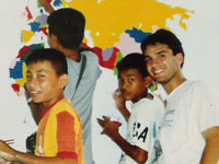 Returned Peace Corps volunteer George Durgerian helps students paint a world map in Thailand.