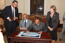 Peace Corps Director Aaron S. Williams, U.S. Ambassador to Tanzania Alfonso E. Lenhardt, and Peace Corps Country Director Andrea Wojnar Diage look on as President Jakaya Kikwete signs a world map that marks the countries Peace Corps volunteers have served since 1961.