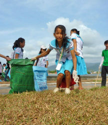 A girl collects trash during a river clean up organized by three Peace Corps volunteers in southern Cambodia.
