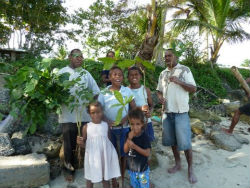 Community members in Peace Corps volunteer Jennifer Diffley's village hold mangrove branches.