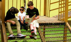 Two students from North Carolina read to a Costa Rican first-grader during the cross cultural home stay.