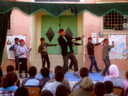 Peace Corps volunteer Josef Saei dances with Moroccan youth during the final workshop presentation.