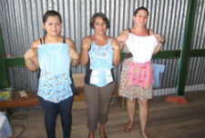 Members of the women's sewing group display a few of their completed products.