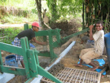 Community members in Madagascar compressing green charcoal materials with a manual ram