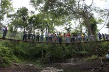 Community members and volunteers pose on the first completed bridge.