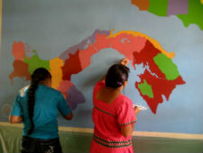 Students in Panama painting a map on the library wall.