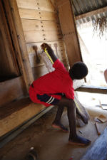 A Surinamese community member measures wood for the new bridge.