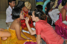 Peace Corps/Thailand volunteer Leanne Klausegger helps prepare a TYT Festival participant for her performance.