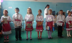 Ukrainian youth, dressed in traditional clothing, perform a song during a school recital.