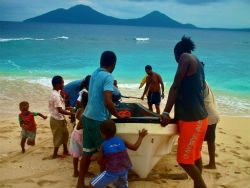 Members of Peace Corps volunteer Stephanie Bergado's small island community pull the health center boat to shore.