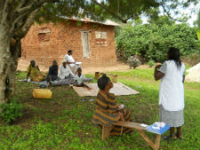Community members in Uganda learn about malaria during a mobile health clinic session.