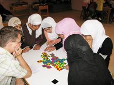 Peace Corps volunteer James Garrett helps Jordanian girls complete a Brain Camp exercise.
