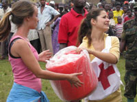 Volunteers Claudia Quintas (left) and Mona Sharif work with red cross workers to unload emergency supplies.