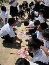 Local Panamanian children work on an art project using recycled materials with Peace Corps volunteer Ashley Gleason.