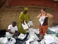 Camille Hogan, a Peace Corps Volunteer in Senegal, helps distribute mosquito nets.