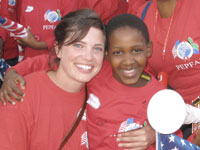 Volunteer Joanna Balza poses for a photo with a young student.