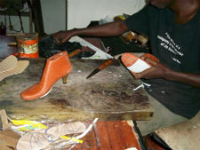 A Senegalese leather worker sizes shoe soles to a model foot.