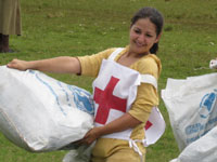 Peace Corps volunteers Mona Sharif and Greg Hoffman carry bags of relief supplies.