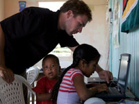 Timothy Morin, a community health volunteer in Guyana, teaches literacy, computer, and science classes to primary schoolchildren.