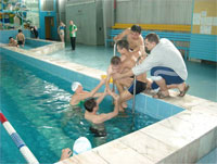 Volunteer and locals help youth into pool