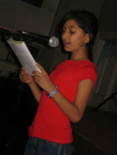 A youth participant reads during open mic night.