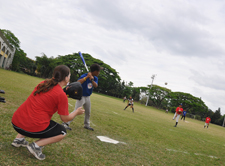 A Peace Corps volunteer plays baseball with youth in the Philippines.